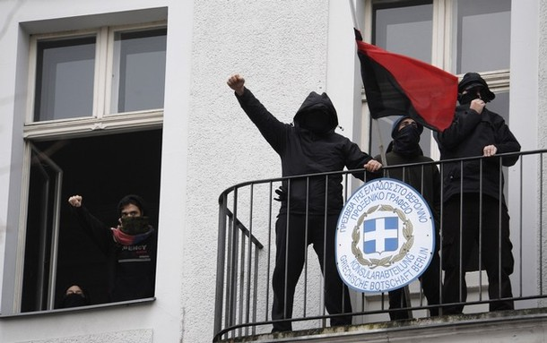 Greek demonstrators stand on the balcony of the Greek consulate in Berlin on December 8, 2008