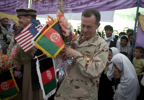 "Navy Adm. Mike Mullen, chairman of the Joint Chiefs of Staff is showerd gifts and flowers from grateful villagers at the opening of the Pushghar Village Girls School, Panjshir Valley, Afghanistan, July 15, 2009. The school located in a remote valley 60 miles north of the capitol Kabul was built by ""Three Cups of Tea"" author Greg Mortenson to promote and support community-based education, especially for girls, in remote regions of Pakistan and Afghanistan."