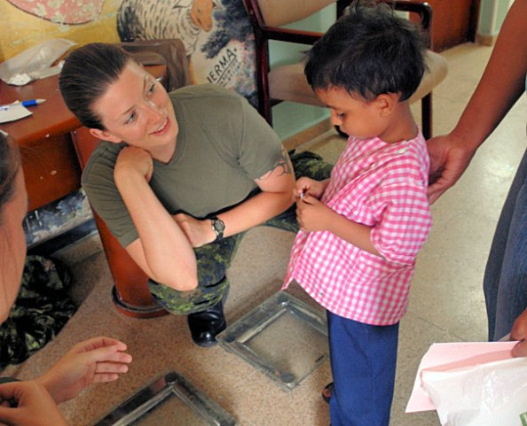 SANTA MARTA, Colombia (Aug. 29, 2008) Canadian Army Capt. Kim Templeton, embarked aboard the amphibious assault ship USS Kearsarge (LHD 3), gives a sticker to a young boy at a neighborhood clinic during the humanitarian assistance mission Continuing Promise (CP) 2008. Kearsarge is supporting the Caribbean phase of CP 2008, an equal-partnership mission between the United States, Canada, the Netherlands, Brazil, Nicaragua, Panama, Colombia, Dominican Republic, Trinidad and Tobago and Guyana. (U.S. Navy photo by Mass Communication Specialist 2nd Class Gina Wollman/Released)