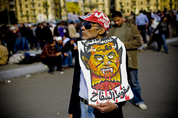 The fall of the killer سقوط السفاح  Protester carrying anti-Mubarak poster in Tahrir Square