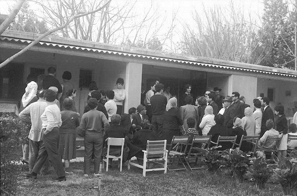 "Photo, John Allison: 1964 Reception for a wedding at Kibbutz Dafna, in the Upper Galil Valley. Each pillar divides another apartment of an individual or a couple. All the children lived in the children's dormitory. Each of these ""studio apartments"" had a sink, small two-burner gas counter-stove of cast iron, a toilet with a shower, and a room slightly divided from the kitchen and bathrooms, with one or two beds. All adults ate meals served at the dining room, or mess hall; the children had their own cafeteria."