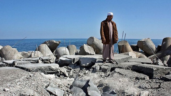 A Libyan man stands on Sirte's bombed fishing harbour. May 12, 2011.