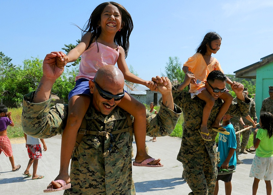 U.S. Marine Corps Staff Sgt. Ruben Ramirez, left, a warehouseman, and Cpl. David Long, a packing specialist, both with Combat Logistics Regiment 35, 3rd Marine Logistics Group, III Marine Expeditionary Force, carry students at Maruglo Elementary School in Capas, Tarlac province, Philippines, April 12, 2013, during a community relations event as part of Balikatan 2013. Balikatan is an annual bilateral training exercise designed to increase interoperability between the Armed Forces of the Philippines and the U.S. military when responding to future natural disasters. (DoD photo by Tech. Sgt. Jerome S. Tayborn, U.S. Air Force/Released)