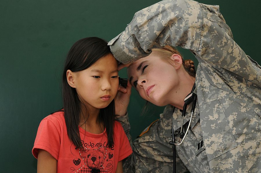 U.S. Army Capt. Tori Schmidt, right, a physician assistant with the 297th Battlefield Surveillance Brigade, Alaska Army National Guard, examines a patient during a medical humanitarian civic action outreach project as part of Khaan Quest 2012 Aug. 14, 2012, in Ulaanbaatar, Mongolia. Khaan Quest is an annual multinational operational exercise co-sponsored by the Mongolian armed forces and U.S. Pacific Command that is executed by U.S. Army Pacific with support from the U.S. State Department. It is designed to strengthen the capabilities of U.S., Mongolian and other nations' forces in international peace support operations worldwide. (DoD photo by Sgt. Edward Eagerton, U.S. Army/Released)