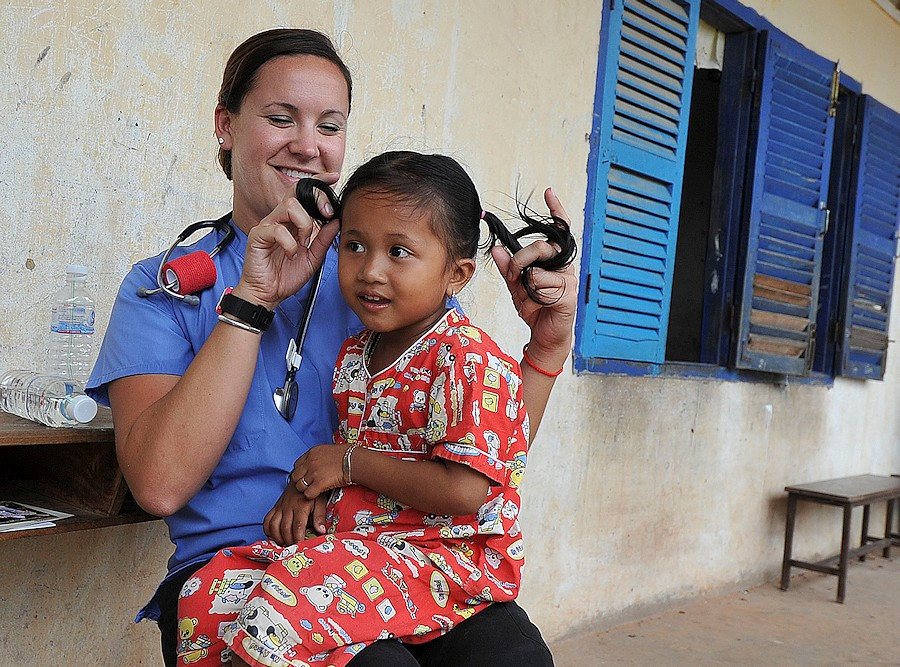 Jacquelyn Bilbro, a registered nurse, entertains a child during a medical civic action project at Hun Sen Cheungkor Primary Elementary School, in Sihanoukville, Combodia, July 29, 2012, during Pacific Partnership 2012. Pacific Partnership is an annual deployment of forces designed to strengthen maritime and humanitarian partnerships during disaster relief operations, while providing humanitarian, medical, dental and engineering assistance to nations of the Pacific. (DoD photo by Mass Communication Specialist 2nd Class Roadell Hickman, U.S. Navy/Released)