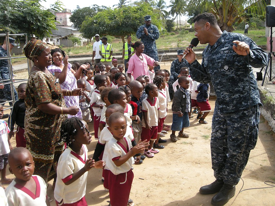 U.S. Navy Musician 2nd Class Kori Gillis, assigned to the U.S. Naval Forces Europe Band ensemble Flagship, sings and dances with children at the Integracao Infantil Cristo Vida school in Nacala, Mozambique, June 21, 2012. Sailors and Marines embarked aboard high speed vessel Swift (HSV-2) visited the school during a community service project as part of Africa Partnership Station (APS) 2012. APS is an international security cooperation initiative facilitated by Commander, U.S. Naval Forces Europe-Africa aimed at strengthening global maritime partnerships through training and collaborative activities in order to improve maritime safety and security in Africa. (DoD photo by Ensign Joe Keiley, U.S. Navy/Released)