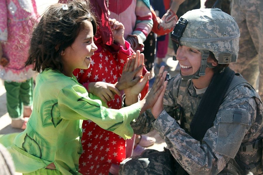 U.S. Army Sgt. Stephanie Tremmel, right, with the 86th Special Troops Battalion, 86th Infantry Brigade Combat Team, interacts with an Afghan child while visiting Durani, Afghanistan, Nov. 1, 2010. Soldiers visited the village to dismantle an old Russian tank, which the villagers will sell for scrap metal to buy food to get through the winter. (DoD photo by Spc. Kristina L. Gupton, U.S. Army/Released)