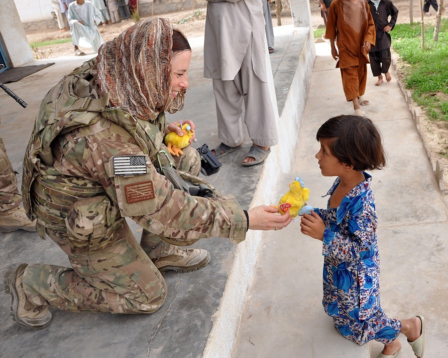 U.S. Navy Lt. j.g. Meghan Burns, with Provincial Reconstruction Team (PRT) Farah, hands a stuffed animal to an Afghan orphan during a key leader engagement at the Farah Orphanage in Farah Province, Afghanistan, Aug. 4, 2013. PRT Farah's mission is to train, advise and assist Afghan government leaders at the municipal, district and provincial levels in Farah province, Afghanistan. (DoD photo illustration by Lt. Chad A. Dulac, U.S. Navy/Released)