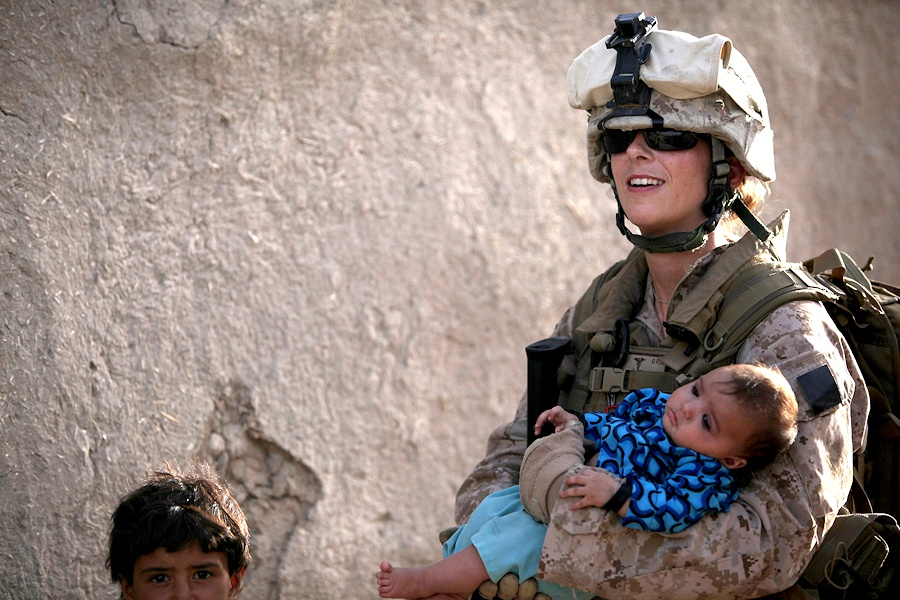 U.S. Navy Petty Officer 2nd Class Claire Ballante holds an Afghan child during a patrol with Marines from 1st Battalion, 2nd Marine Regiment in Musa Qa'leh, Afghanistan, Aug. 3, 2010. Ballante is part of a female engagement team that is patrolling local compounds to assess possible home damage caused by aircraft landing at Forward Operating Base Musa Qala. (DoD photo by Cpl. Lindsay L. Sayres, U.S. Marine Corps/Released)