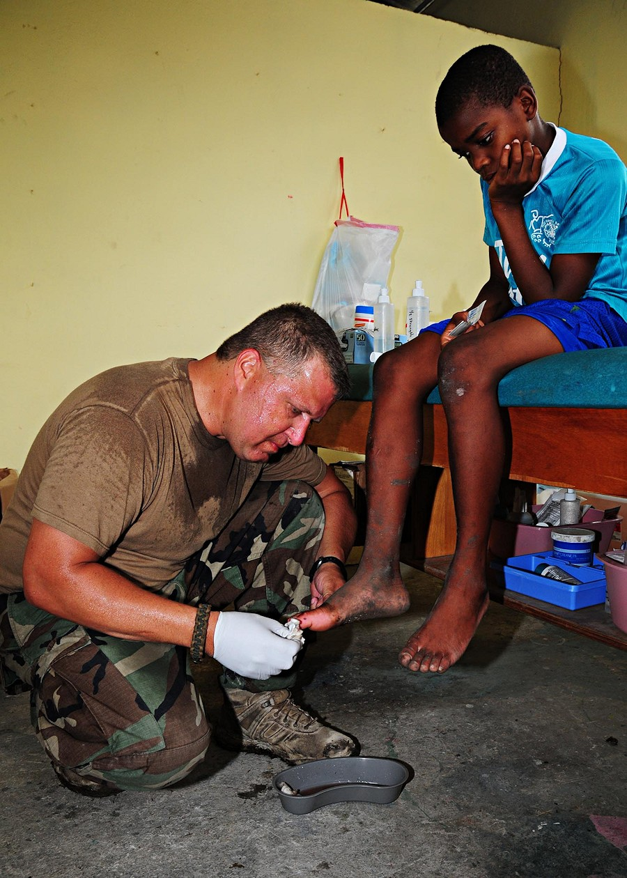 A U.S. Navy hospital corpsman attached to Amphibious Construction Battalion 2 cleans a wound on a Haitian boy's foot during a community relations event at an orphanage in Port-au-Prince, Haiti, Feb. 19, 2010. (DoD photo by Mass Communication Specialist 2nd Class Kim Williams, U.S. Navy/Released)
