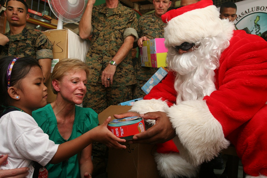 U.S. Marine Corps Master Gunnery Sgt. Joseph Haggins, dressed as Santa Claus, presents a gift to a Filipino child during Operation Goodwill at the Manila Day Care Center in Manila, Philippines, Dec. 16, 2009. The operation gives U.S. Marines and their families stationed in Okinawa, Japan, an opportunity to spread goodwill in the region during the holiday season. (DoD photo by Sgt. Leon M. Branchaud, U.S. Marine Corps/Released)